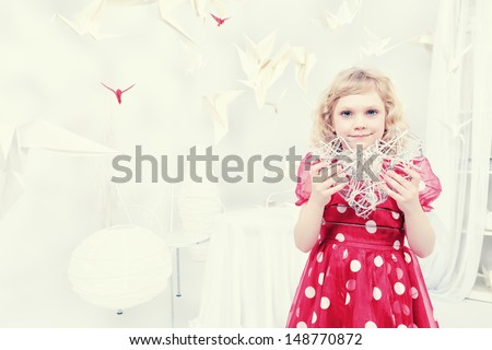 Cute little girl standing in a white room surrounded with paper birds and holding toy heart.