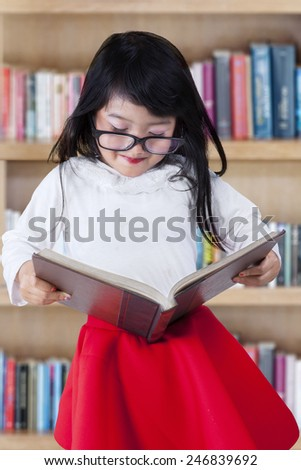 Cute little girl standing in the library while reading a textbook - stock photo