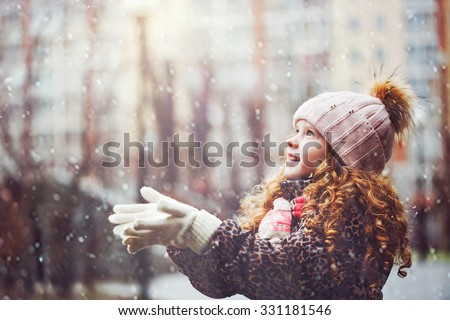 Cute little girl stretches her hand to catch falling snowflakes. First snow. Toning instagram filter. - stock photo