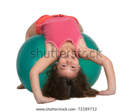Cute little girl stretching on pilates ball - stock photo