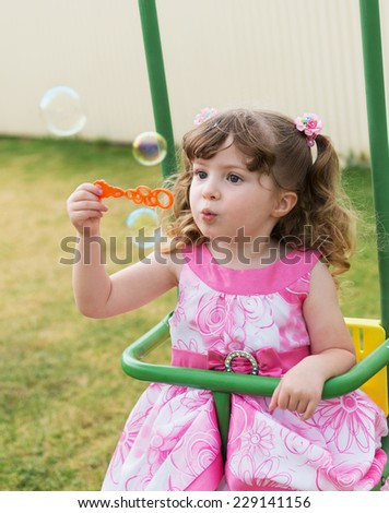 cute little girl swinging on seesaw and playing with soap bubbles - stock photo