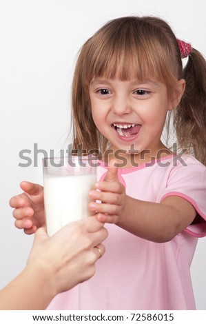 Cute little girl take a glass of milk on light background - stock photo