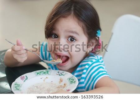 Cute little girl take milk in her breakfast. Focus in her right eye - stock photo