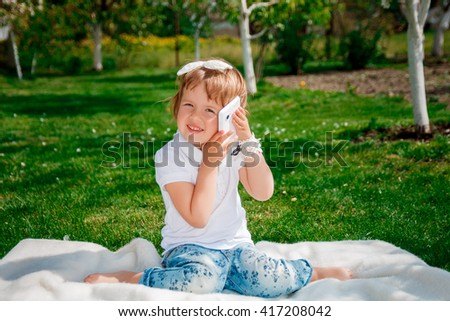 cute little girl talking on the phone. Little baby girl dressed in white polo and jeans, barefooted with mobile phone sitting on the white fur cover in the park - stock photo