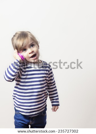 Cute little girl talking with a pink phone isolated. Adorable baby playing to use a mobile - stock photo