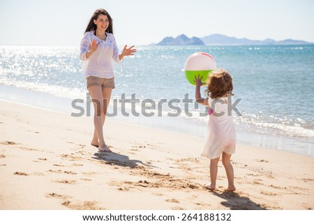 Cute little girl throwing a beach ball at her mom and having some fun on a sunny day - stock photo