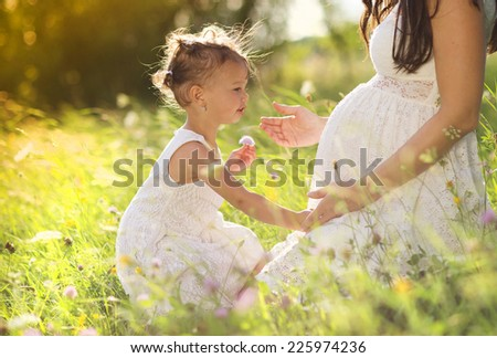 Cute little girl touching her mother's pregnant belly in summer nature - stock photo