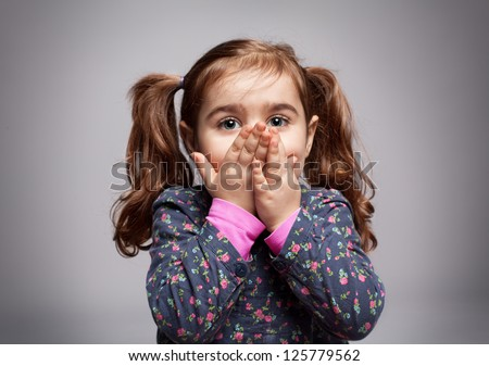 cute little girl trying to blow a kiss on grey background - stock photo