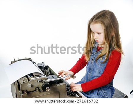 Cute little girl typing letter on vintage typewriter keyboard - stock photo