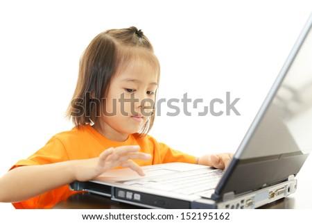 Cute little girl using a laptop - stock photo