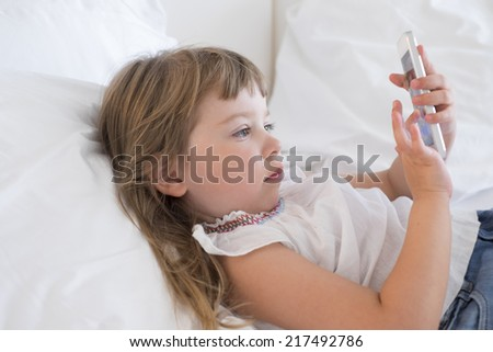 Cute Little girl using mobile phone at home - stock photo