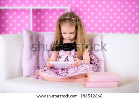 Cute little girl using modern tablet computers on white sofa in the polka-dot bright pink room at home fun game alone instead of reading book - stock photo