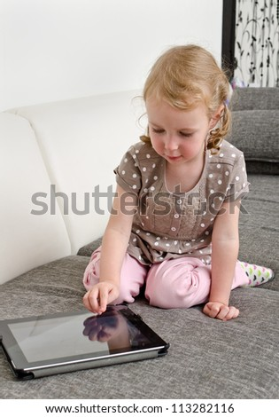 Cute little girl using tablet computer - stock photo