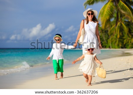 cute little girl walking on beach with family - stock photo