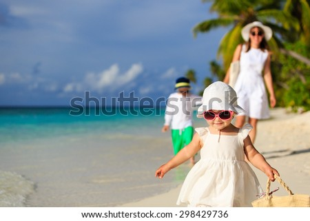 cute little girl walking on the beach with family on background - stock photo