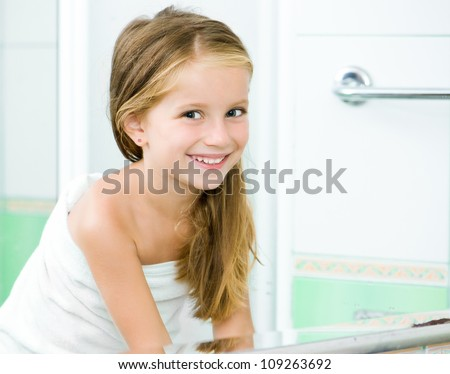 Cute little girl washing in bath. Reflection in the mirror - stock photo