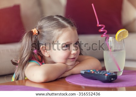 cute little girl watching tv and having lemonade at home. - stock photo