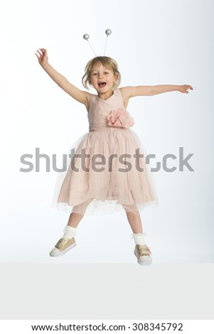 Cute little girl wearing a dress and bumble bee boppers posing in mid air against a white background