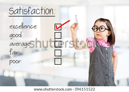Cute little girl wearing business dress and checking excellence on customer satisfaction survey form. Office background.