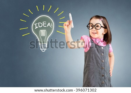 Cute little girl wearing business dress and drawing a light bulb. Blue background.