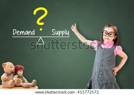 Cute little girl wearing business dress and showing demand and supply compare on balance bar on green chalk board. - stock photo