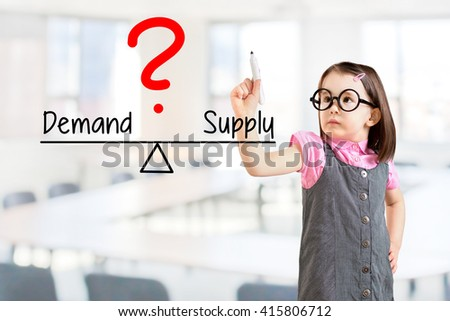 Cute little girl wearing business dress and writing demand and supply compare on balance bar. Office background. - stock photo