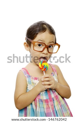 Cute little girl wearing glasses eating her lollipop isolated over white background