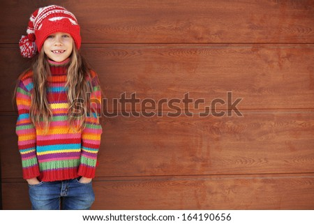 Cute little girl wearing knit winter clothes posing over wooden background - stock photo