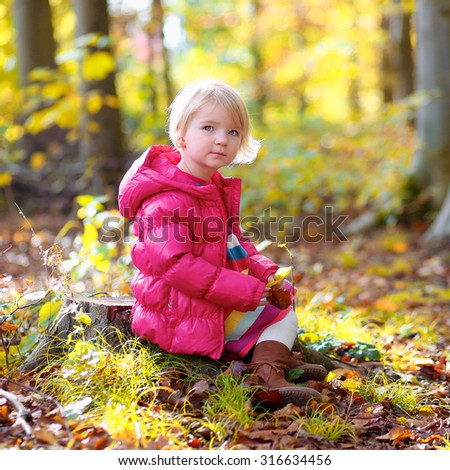 Cute little girl wearing warm pink jacket playing in beautiful autumn forest on sunny fall day - stock photo