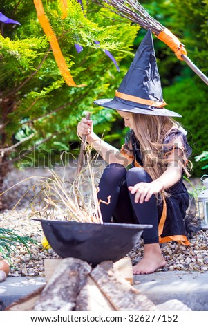 Cute little girl wearing witch costume on Halloween outdoors. Trick or treat. - stock photo