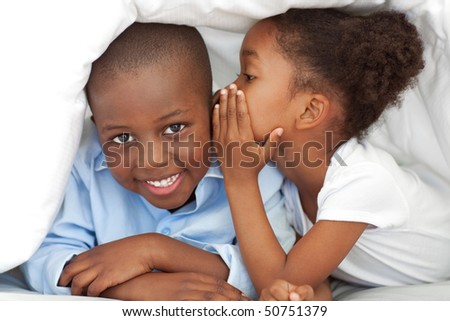 Cute little girl whispering something to her brother under the cover