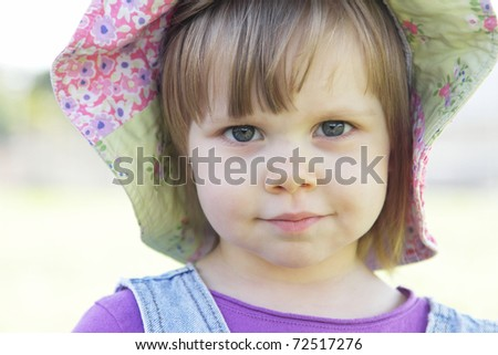 Cute little girl with a hat outdoors - stock photo