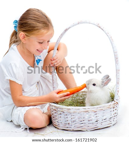 Cute Little girl with a rabbit in a basket on a white background - stock photo