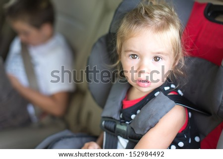 Cute little girl with a serious bewildered expression strapped into a childs safety seat in a vehicle with her young brother visible in the background