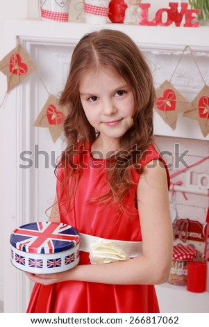 Cute little girl with a sweet smile in red dress holding a box with a flag of the United Kingdom - stock photo