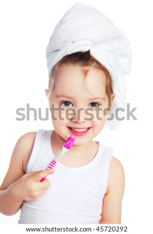 cute little girl with a towel on her head brushing her teeth - stock photo