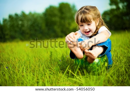 cute little girl with a water-melon on the grass in summertime - stock photo