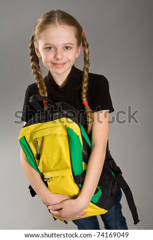 Cute little girl with backpack over grey background - stock photo