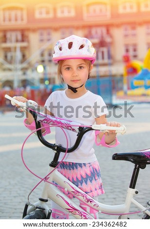 Cute little girl with bicycle having fun outdoors in summer day, training to cycling, happy childhood, enjoying active life - stock photo