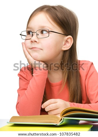 Cute little girl with black glasses is dreaming while reading book, isolated over white - stock photo
