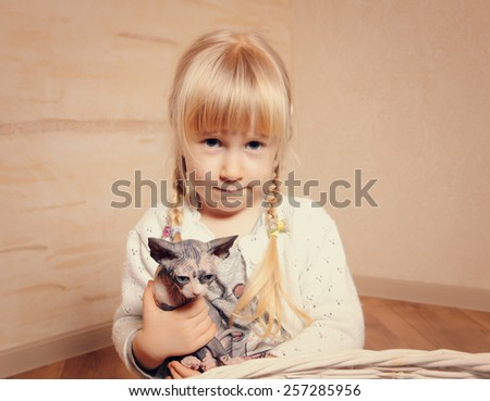 Cute little girl with blond pigtails cuddling a small sphynx kitten holding it gently in her arms with an smile of affection - stock photo