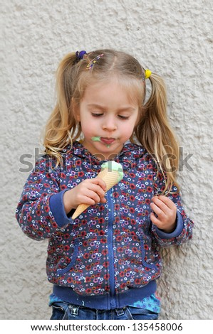 Cute little girl with blonde hair and pigtails eating ice cream - stock photo
