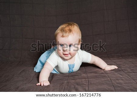 Cute little girl with blue eyes lying on the bed