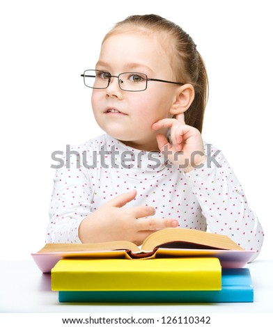 Cute little girl with books and glasses holding hand near her ear like listening to something, isolated over white - stock photo