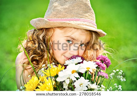 Cute little girl with charming curly hair on a meadow in summer day. - stock photo