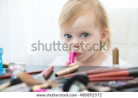 Cute little girl with cosmetics and mirror.
