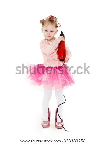 Cute little girl with curlers on her head dressed in pink clothes and a huge mother's shoes holds a hair dryer on a white background. Little fashionista.  3 year old. - stock photo