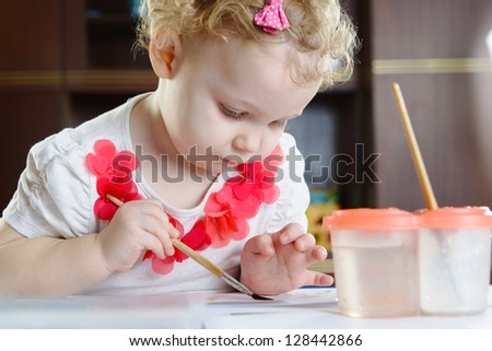 Cute little girl with curly hair painting at home