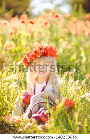 Cute little girl with flower garland in the poppy field at sunset - stock photo