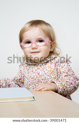 Cute little girl with glasses standing near desk